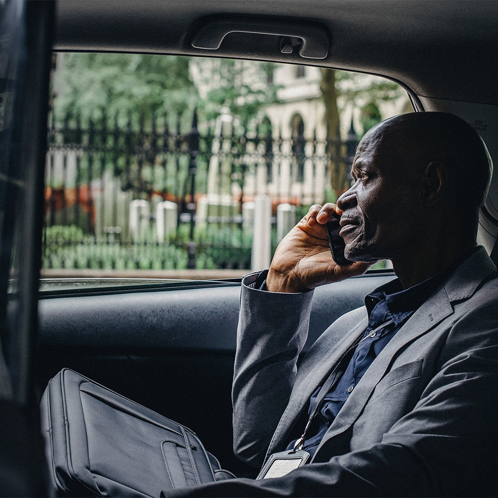 corporate traveller uses phone whilst travelling for work in car