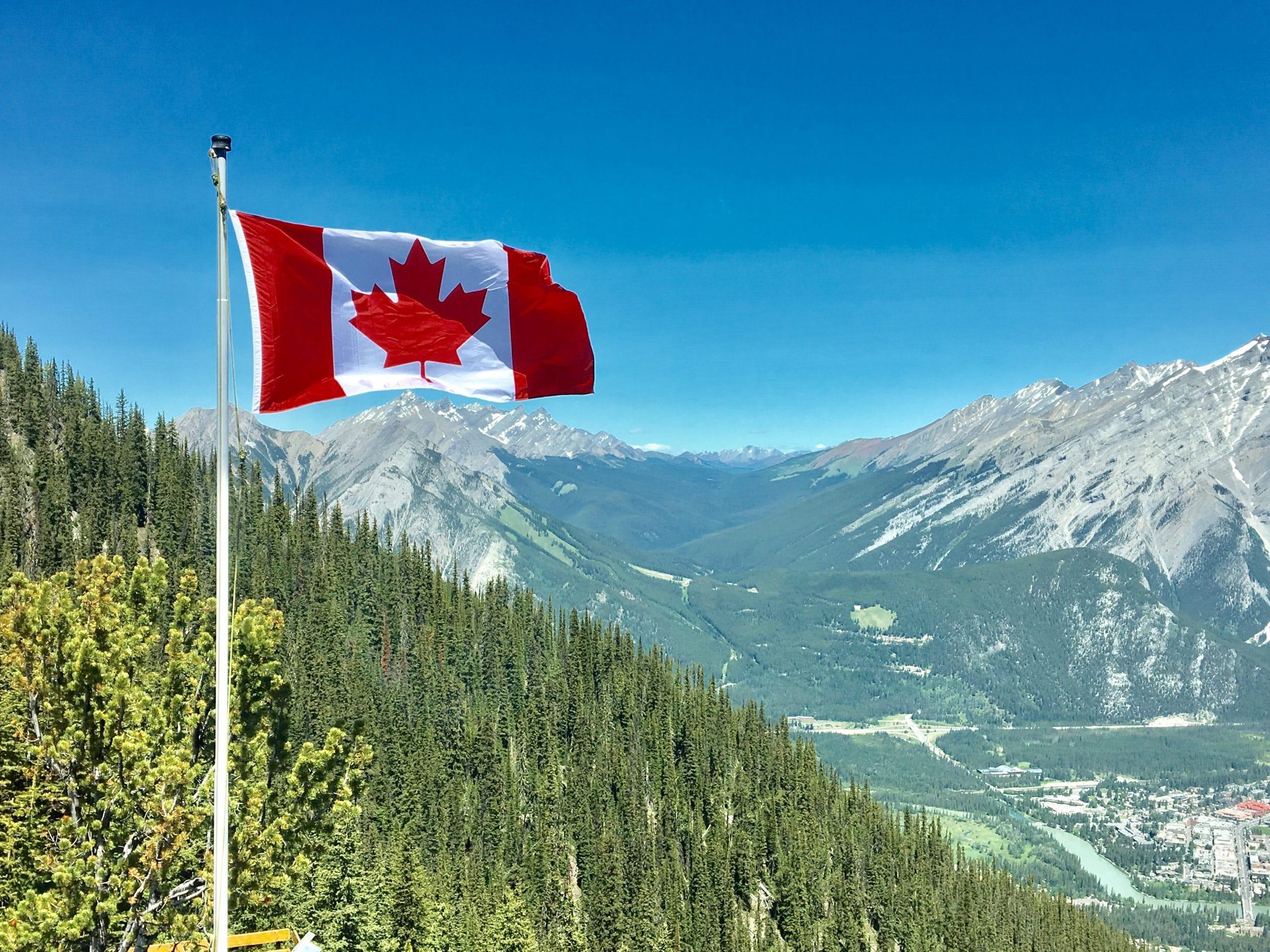 Canadian flag flies over bc mountains as Canada reopens it's borders
